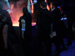 The 2084 ensemble gather around a bonfire to burn propaganda. They are wearing blue armbands.