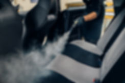 Carwash, worker cleans seats with steam