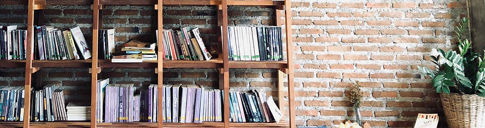 a wooden bookshelf against a brick wall