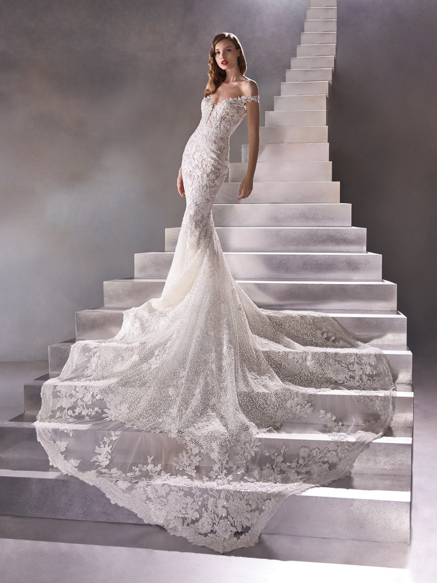 A Pronovias off the shoulder lace and mesh mermaid fit and flare wedding dress with a train