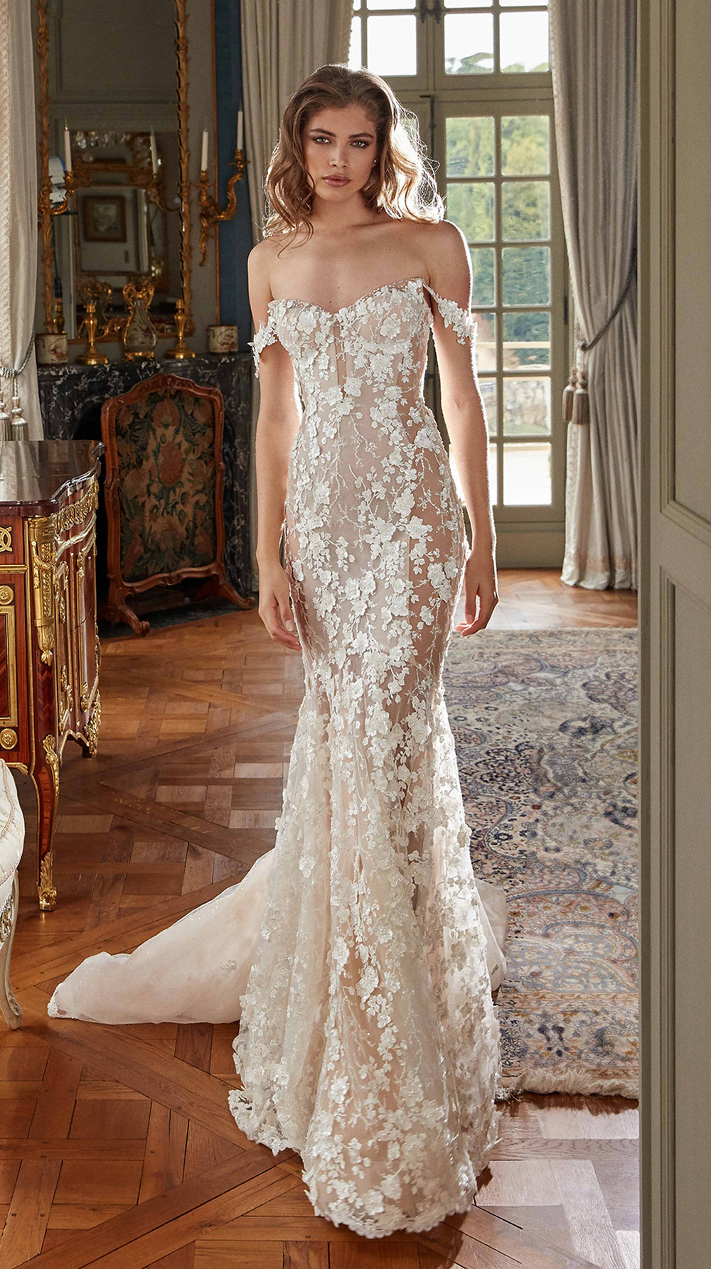 A fitted, semi-sheer mermaid wedding gown with light 3D embroidered flowers over silk tulle combines with elegant off-the-shoulder straps, a low illusion back, and sheer inserts on the sides that flow into a dramatic caviar tulle train