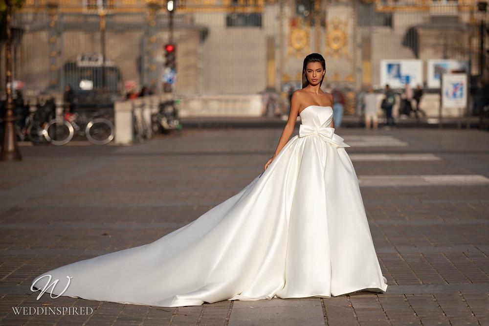 A Milla Nova strapless princess ball gown wedding dress with a bow