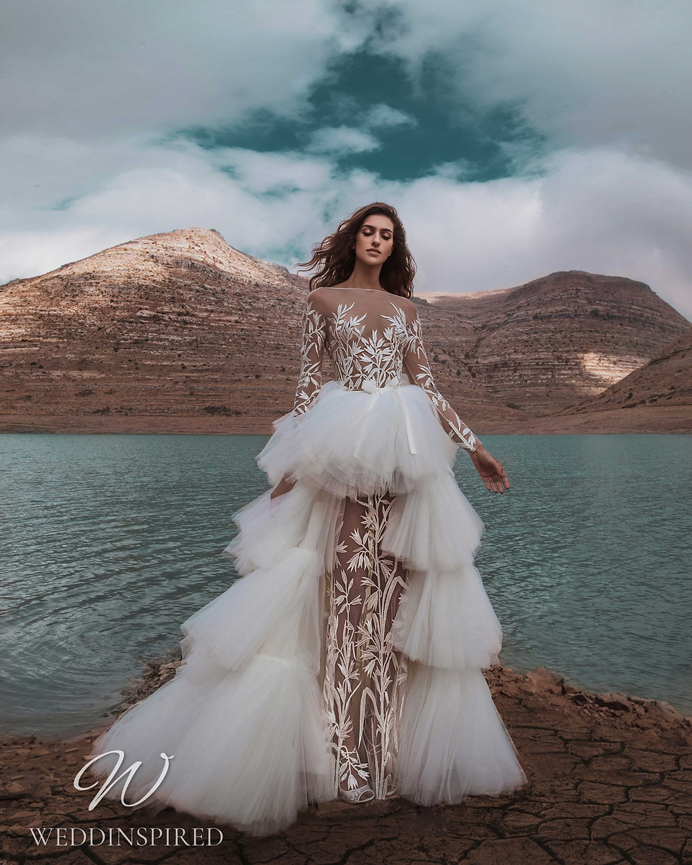 A Zuhair Murad Fall 2021 white illusion mermaid wedding dress with long sleeves and a ruffle tulle detachable skirt