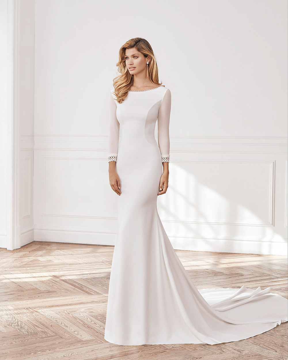 An Aire Barcelona 2020 simple crepe mermaid fit and flare wedding dress with long sleeves and a train