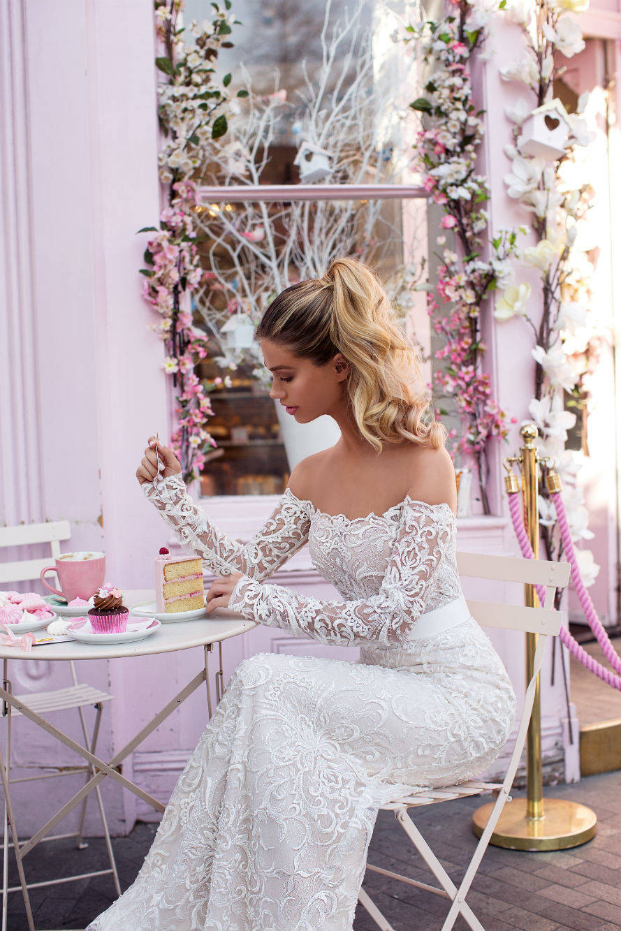 An off the shoulder lace A-line white wedding dress with long sleeves