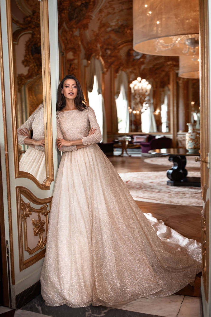 A Milla Nova modest sparkly blush ball gown wedding dress with long sleeves