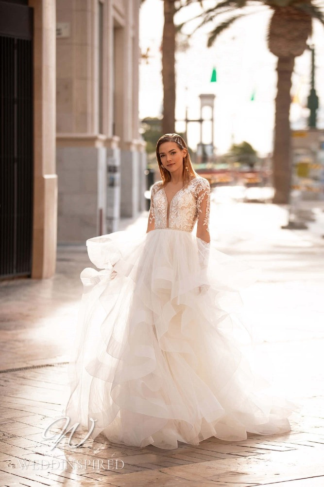 A Nora Naviano 2021 lace and tulle A-line wedding dress with a ruffle layered skirt