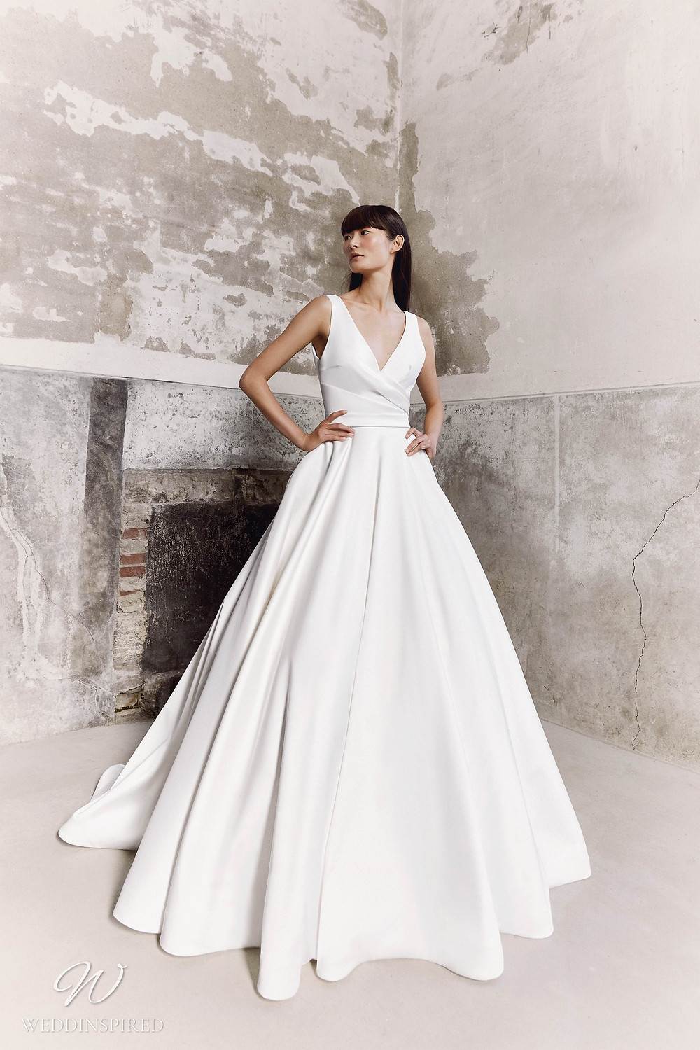 A Viktor & Rolf Fall/Winter 2021 simple satin ball gown wedding dress with straps and a v neckline