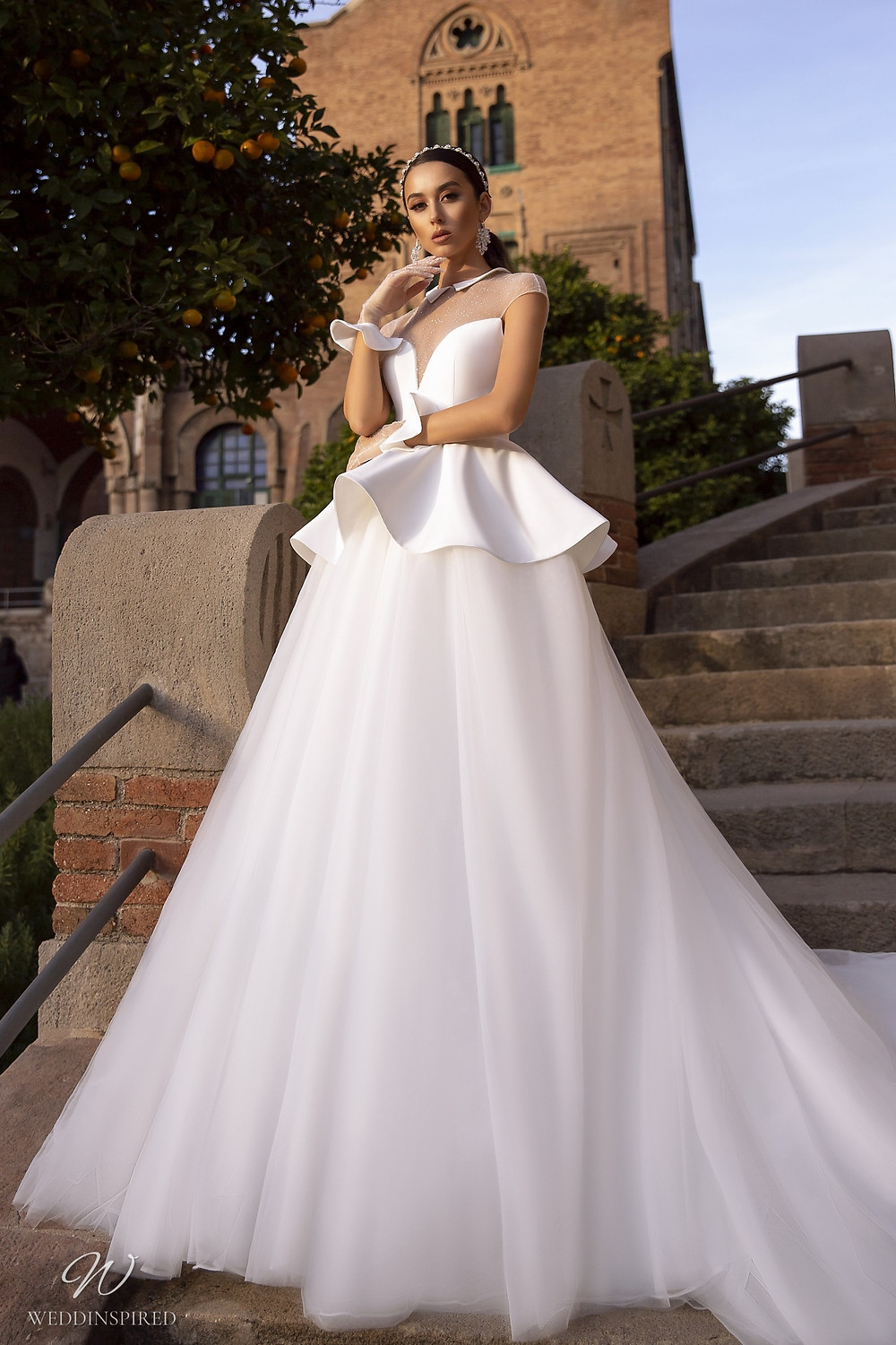 A Maks Mariano tulle ball gown wedding dress with a peplum and an illusion top