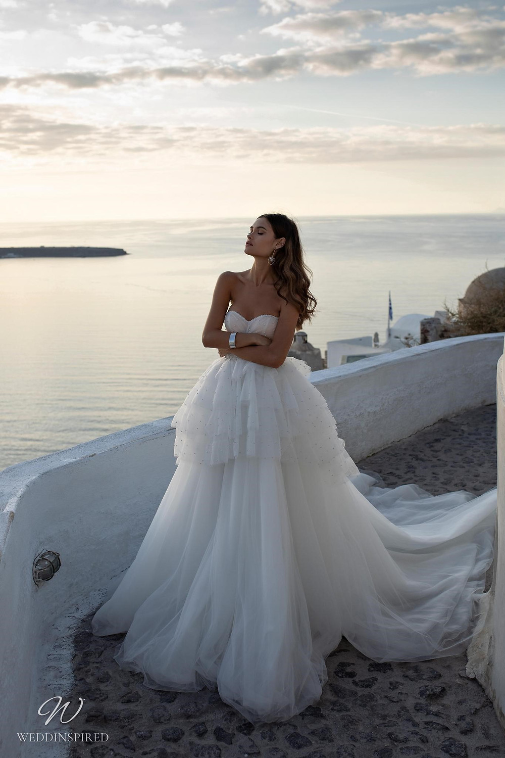A Ricca Sposa strapless tulle ball gown wedding dress with a layered ruffle skirt and a sweetheart neckline