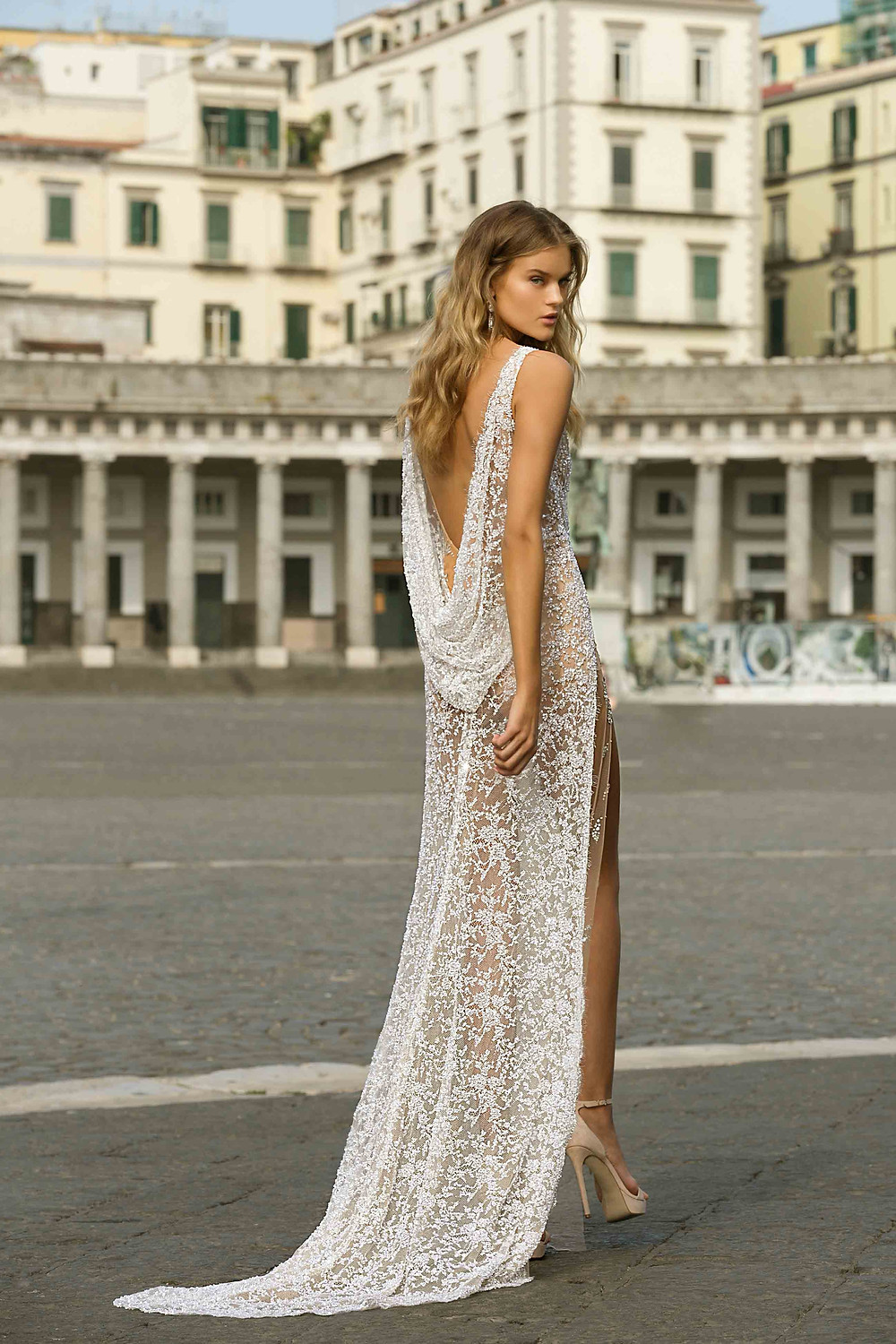 A lace wedding dress, with a high slit, long train and a cowl back