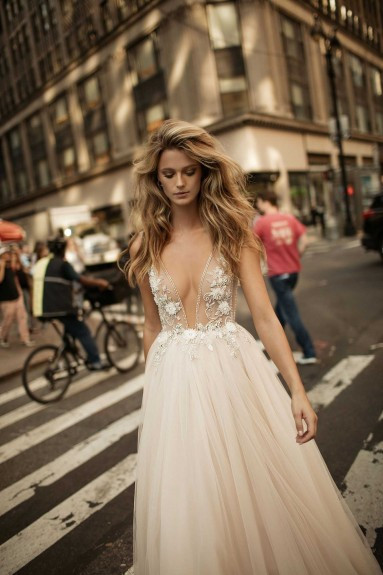 A blush, tulle ball gown wedding dress, with low v neckline and flowers