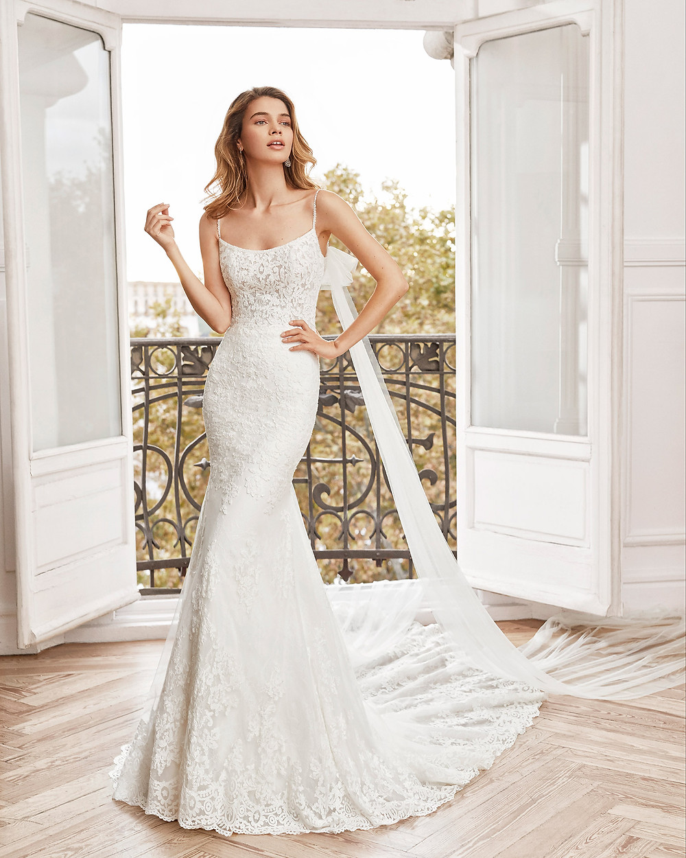 An Aire Barcelona 2020 lace mermaid fit and flare wedding dress with thin straps and a train