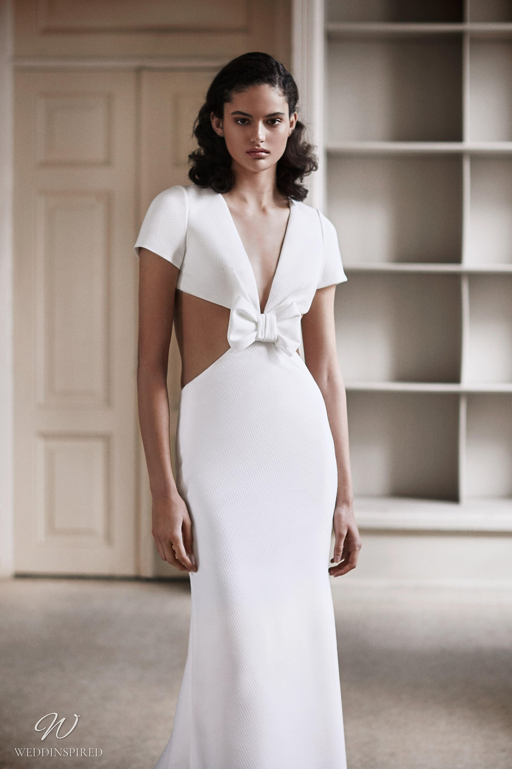 A Viktor & Rolf 2021 mermaid wedding dress with side cut outs and a bow