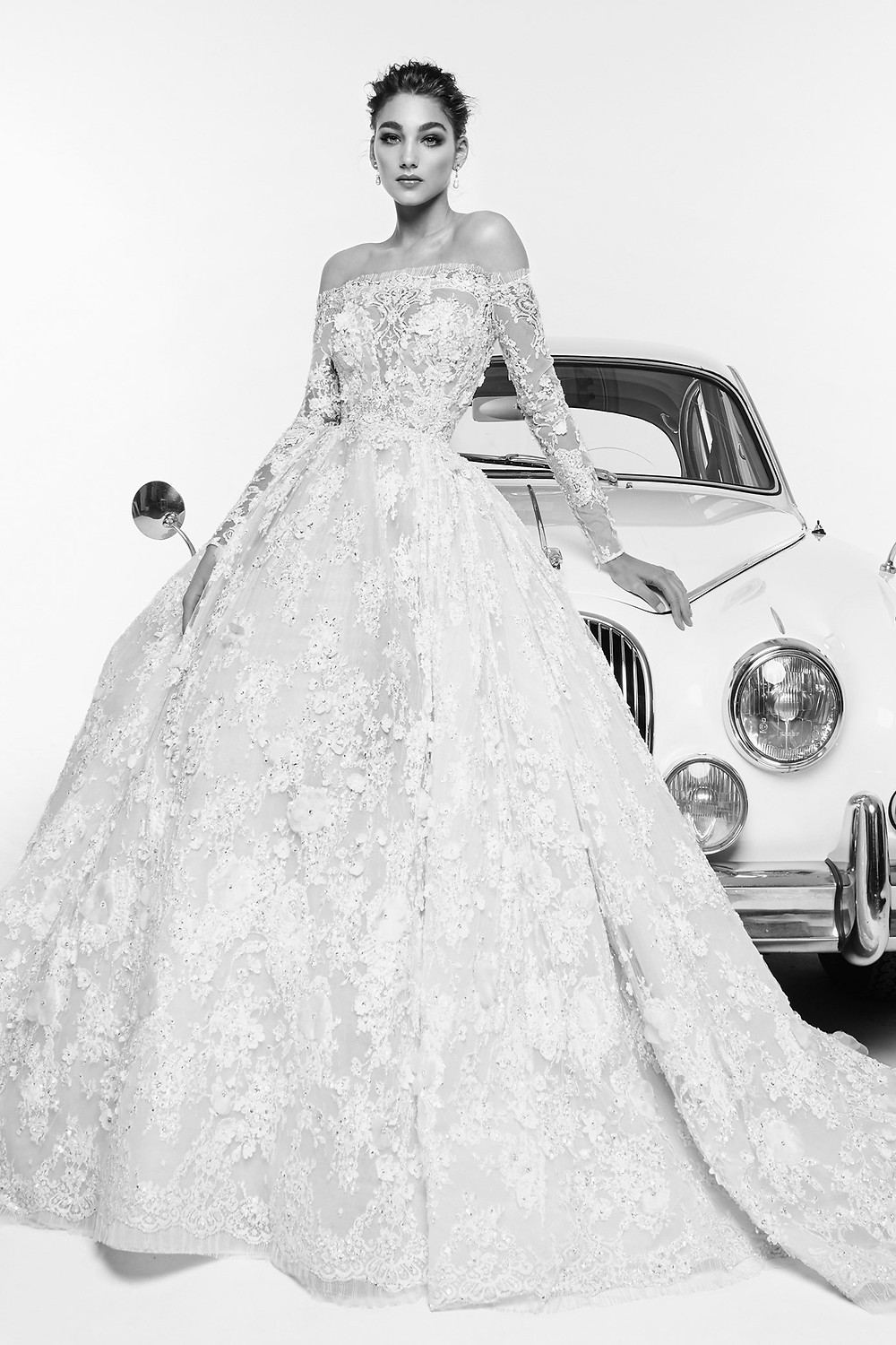 An off the shoulder, lace ball gown wedding dress, with long sleeves
