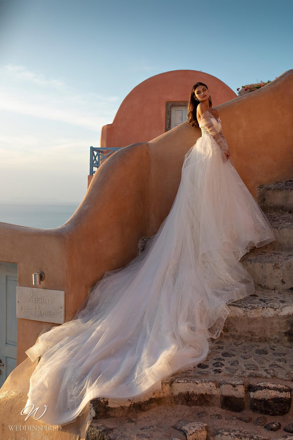 A Ricca Sposa off the shoulder tulle ball gown wedding dress with long sleeves and a train