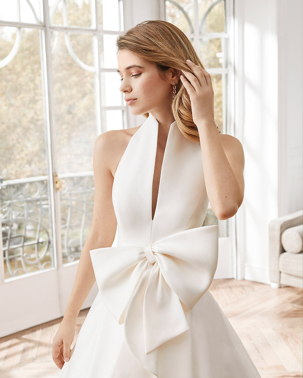 An Aire Barcelona 2020 simple silk A-line wedding dress with a high neckline and a big bow