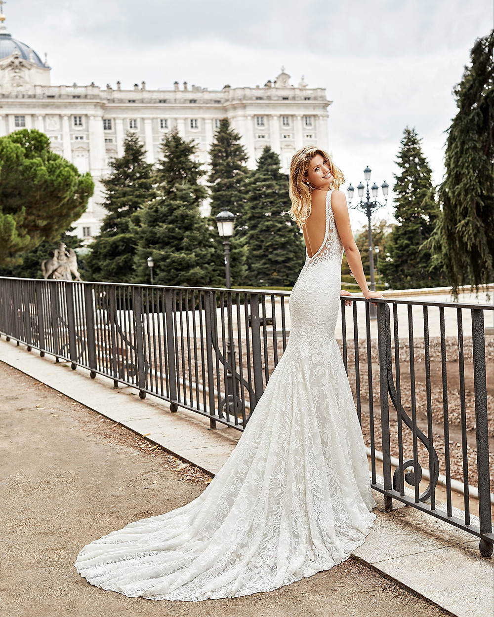 An Aire Barcelona 2020 romantic lace mermaid fit and flare wedding dress with a low back and a train