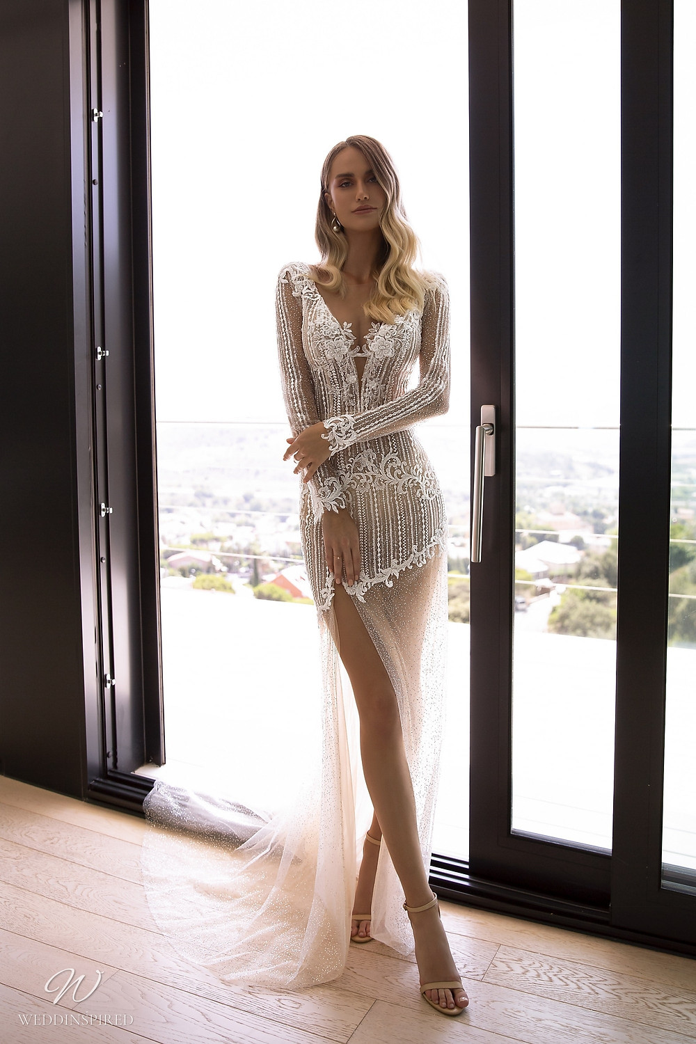 A Tina Valerdi sexy lace fitted wedding dress with tulle, long sleeves and a high slit