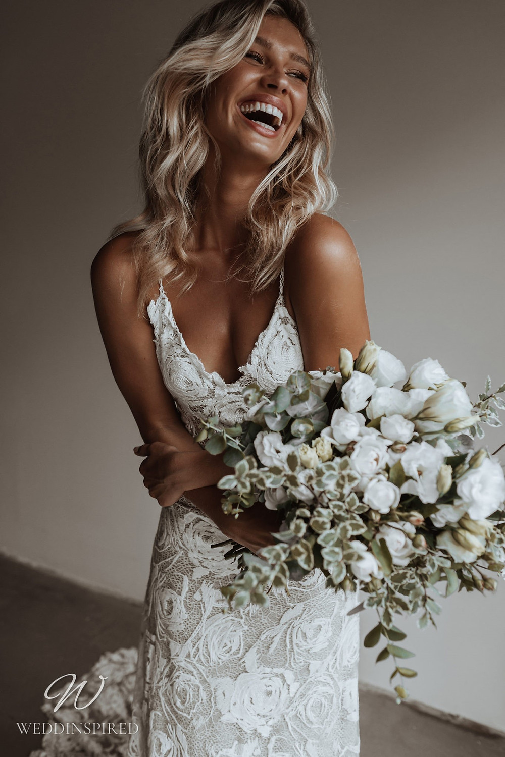 A Grace Loves Lace A-line wedding dress with lace and rose design and a train and thin spaghetti straps