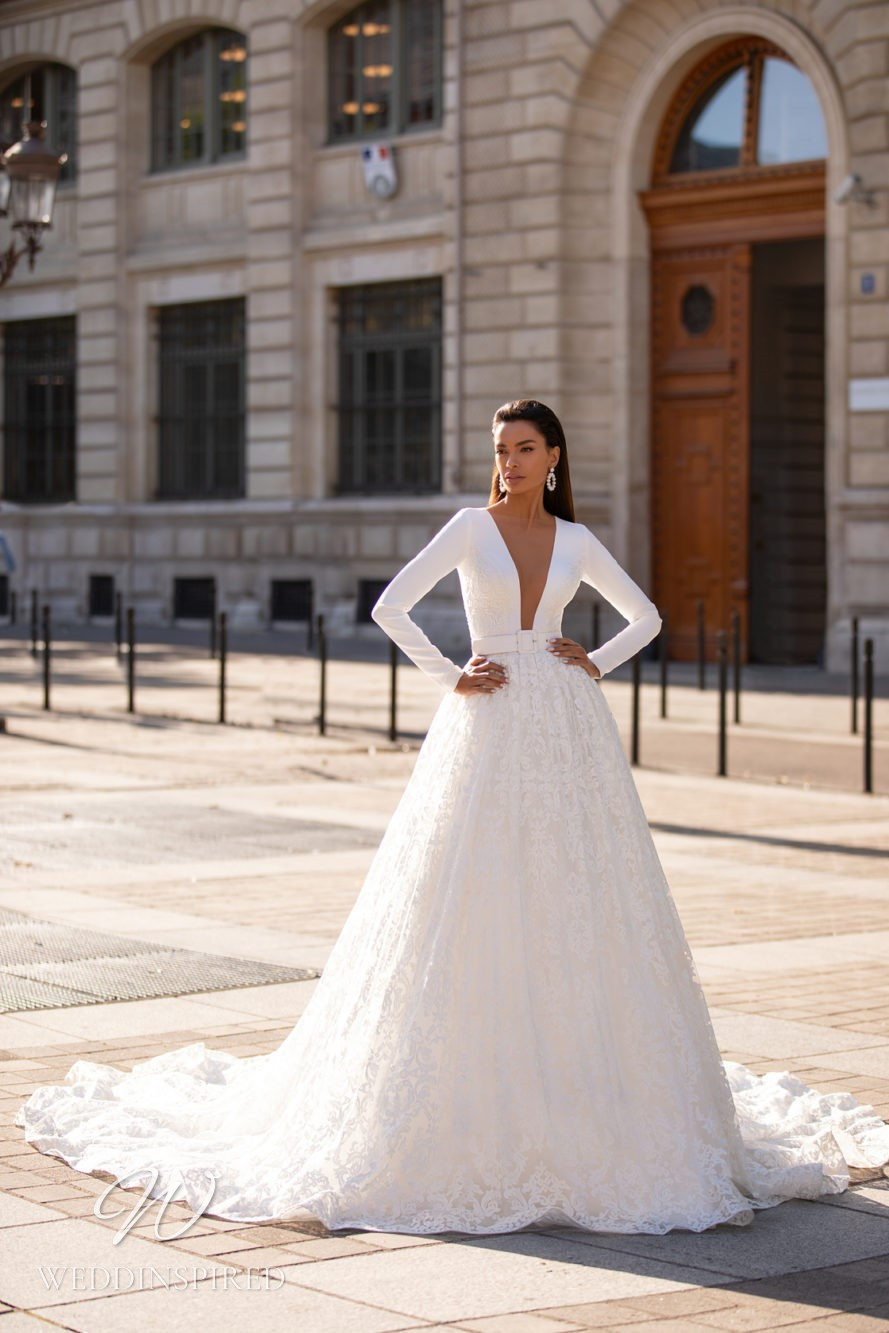 A Milla Nova lace ball gown wedding dress with long sleeves and a deep v neckline