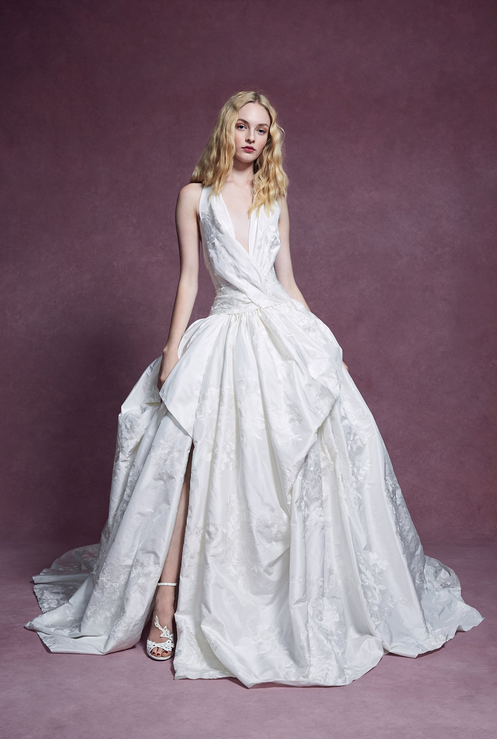 A Marchesa 2020 ball gown wedding dress with a low v halterneck and big skirt with embroidery