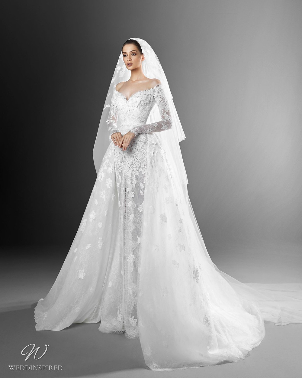 A Zuhair Murad mermaid off the shoulder wedding dress with lace, long sleeves, a detachable skirt and a veil