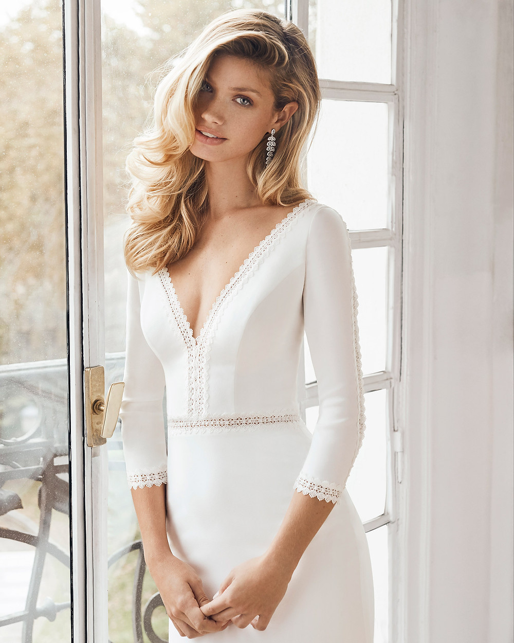 An Aire Barcelona 2020 simple mermaid fit and flare crepe wedding dress with long sleeves and a low v neckline