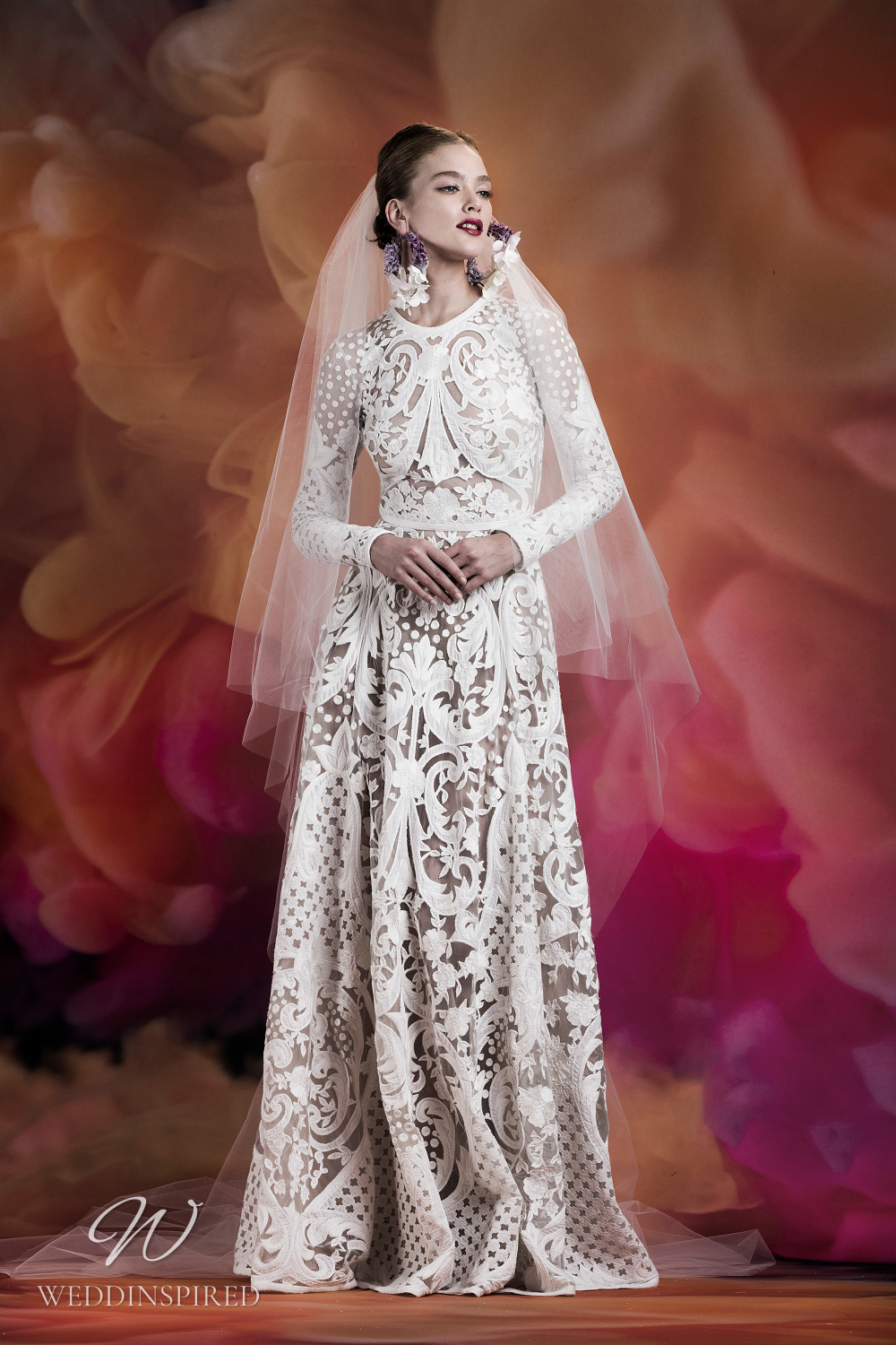 A Naeem Khan modest intricate lace A-line wedding dress with long sleeves and a high neckline