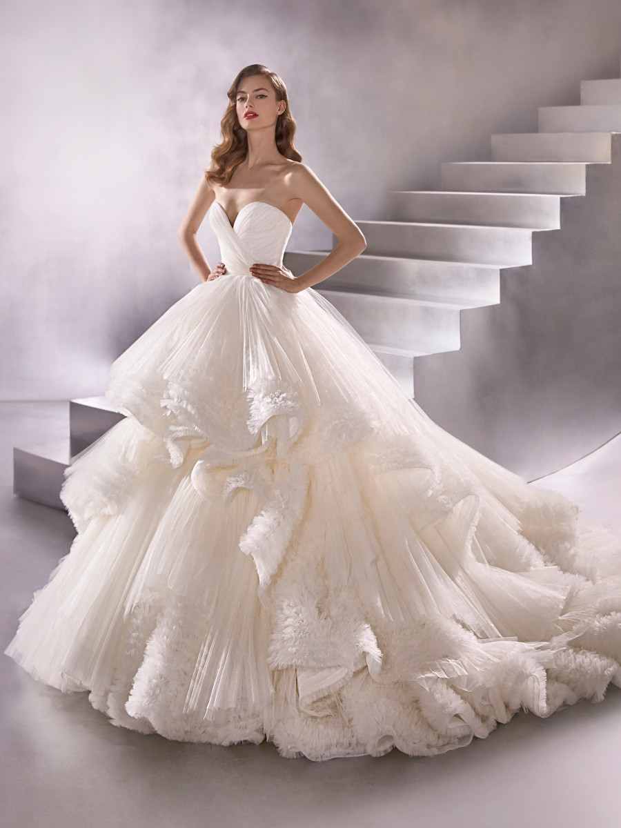 A Pronovias strapless ball gown wedding dress with a layered tulle and skirt
