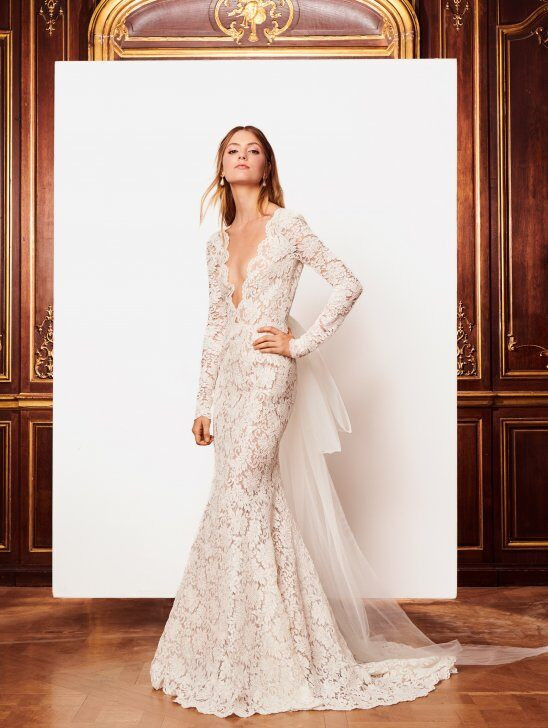 An Oscar de la Renta lace mermaid fit and flare wedding dress with long sleeves and a low v neckline