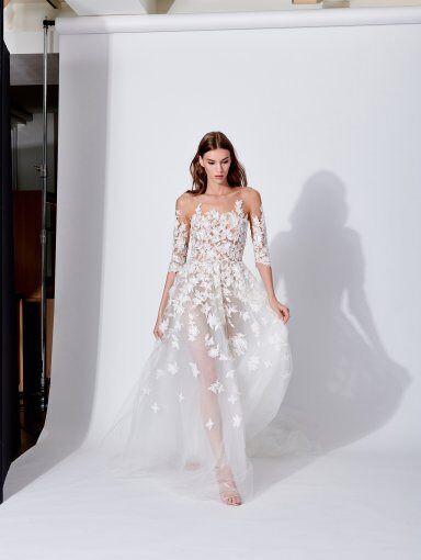 A Oscar de la Renta 3/4 sleeve, A-line wedding dress, with a tulle skirt, lace and flowers