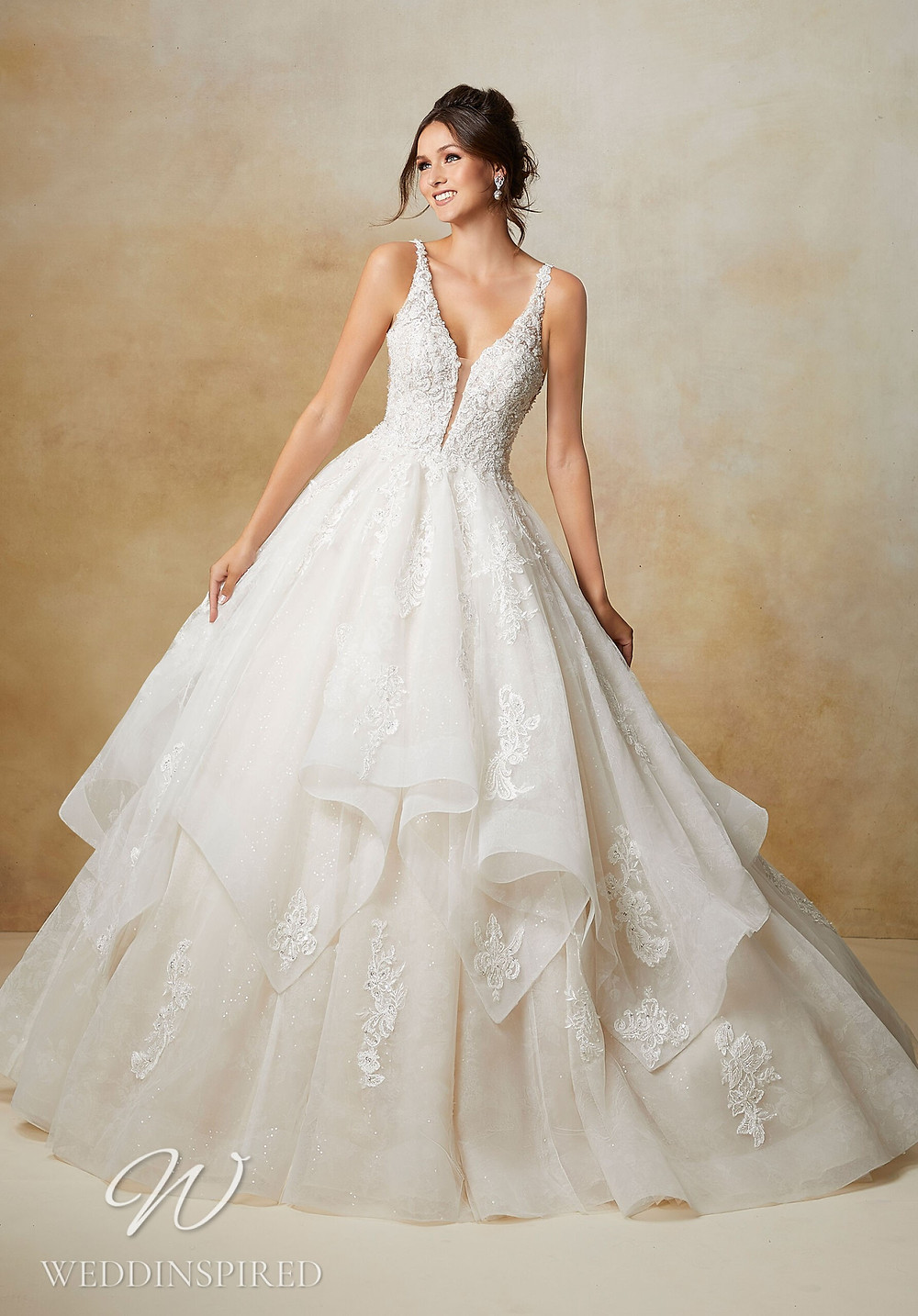 A Madeline Gardner lace ball gown wedding dress with a ruffle skirt and straps