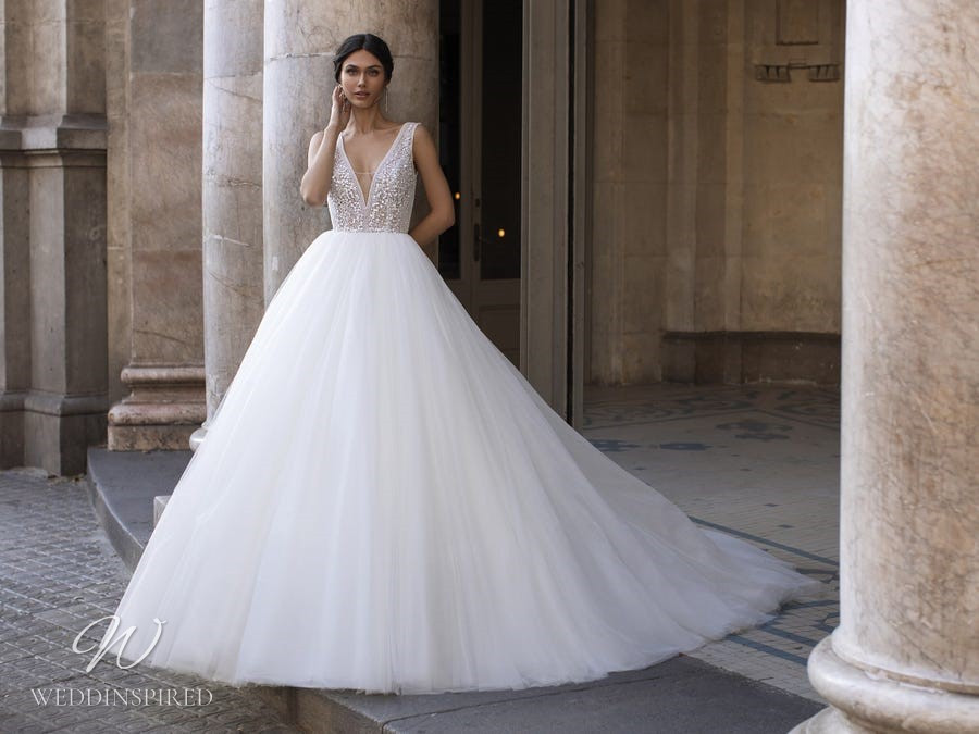 A Pronovias Privée 2021 sparkly lace and tulle princess ball gown wedding dress with a v neck and straps