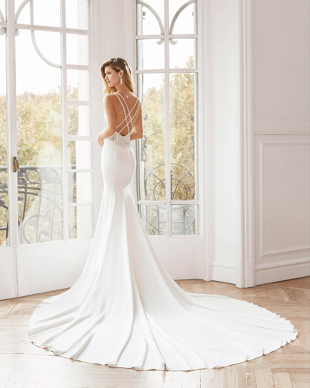 An Aire Barcelona 2020 sexy crepe mermaid fit and flare wedding dress with a low back, thin spaghetti straps and a train