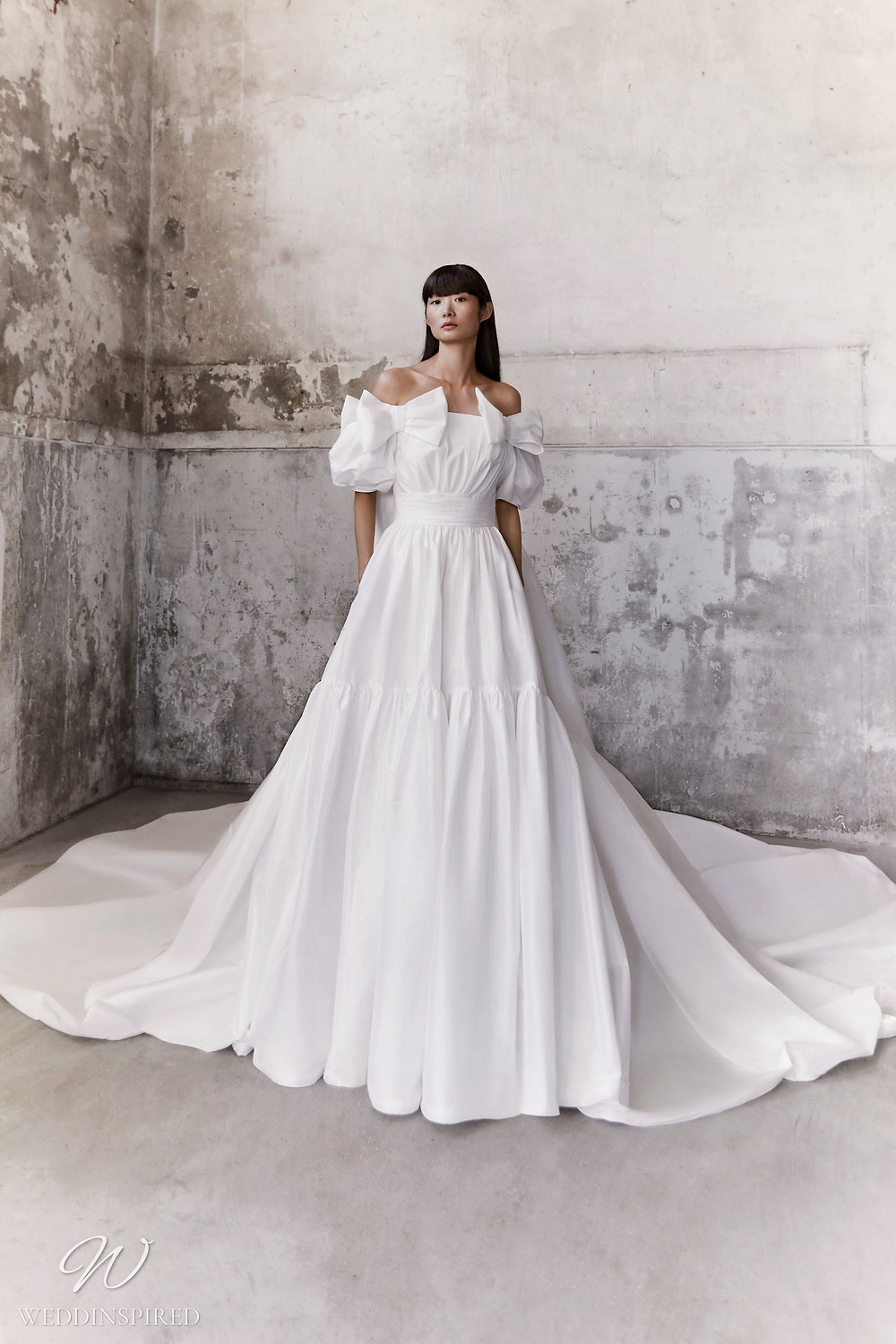 A Viktor & Rolf Fall/Winter 2021 simple off the shoulder A-line wedding dress with bows and a train