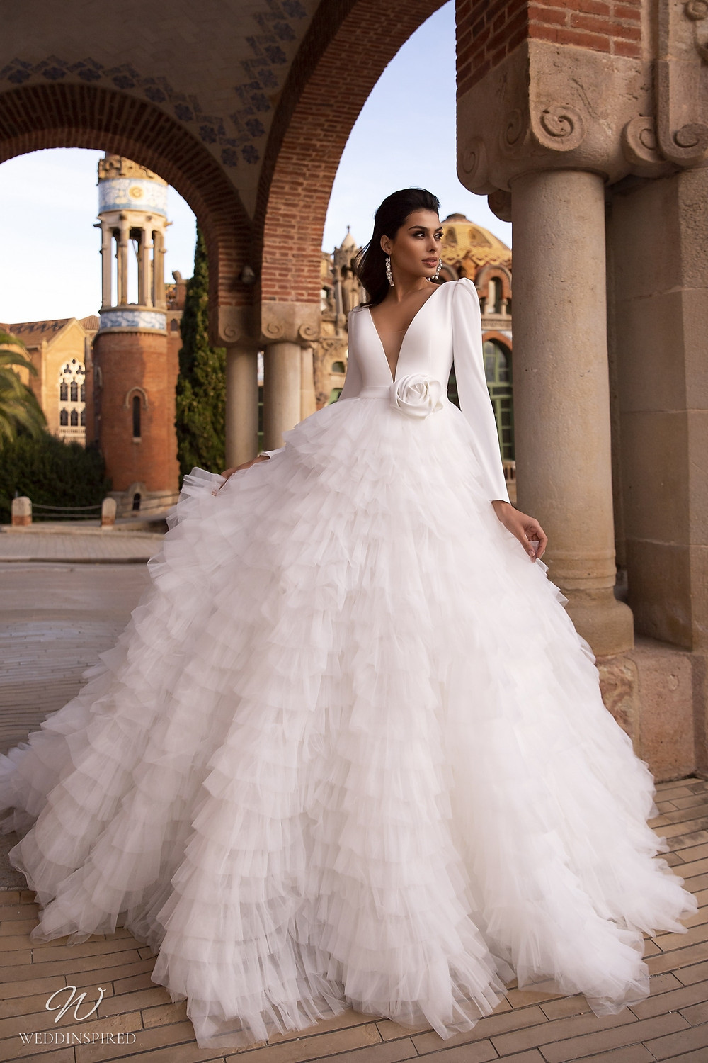 A Maks Mariano ball gown wedding dress with long sleeves and a layered tulle ruffle skirt