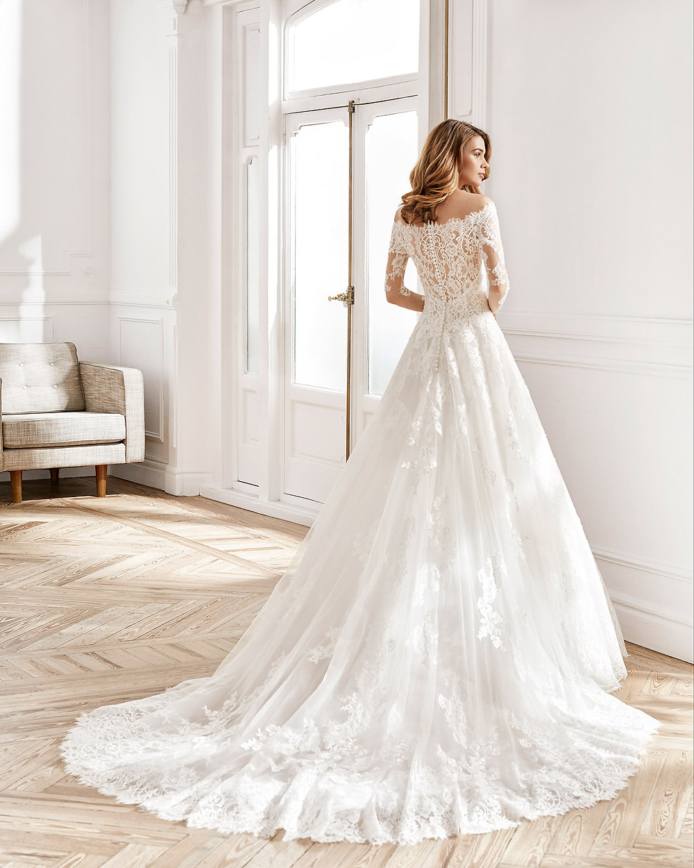 An Aire Barcelona 2020 off the shoulder lace ball gown wedding dress with long illusion sleeves