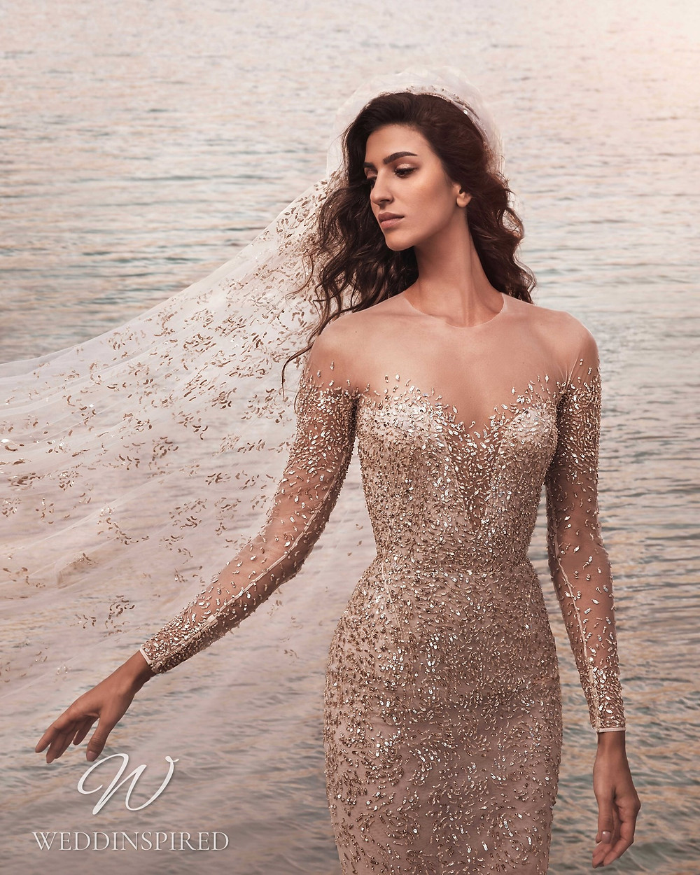 A Zuhair Murad Fall 2021 blush sparkly mermaid wedding dress with long sleeves and an illusion neckline