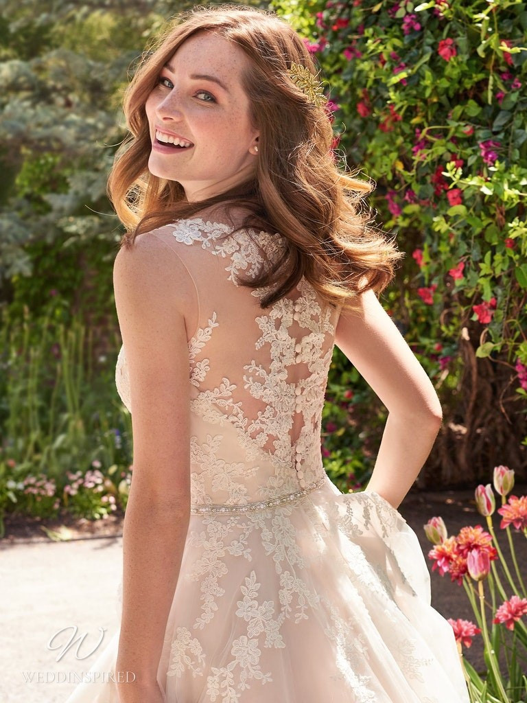 A Rebecca Ingram 2020 blush tulle and lace A-line wedding dress with an illusion back
