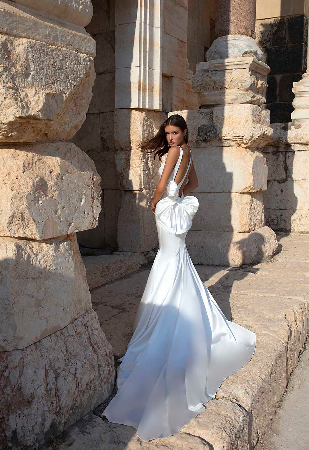A Pnina Tornai silk mermaid fit and flare wedding dress with a low back and a bow