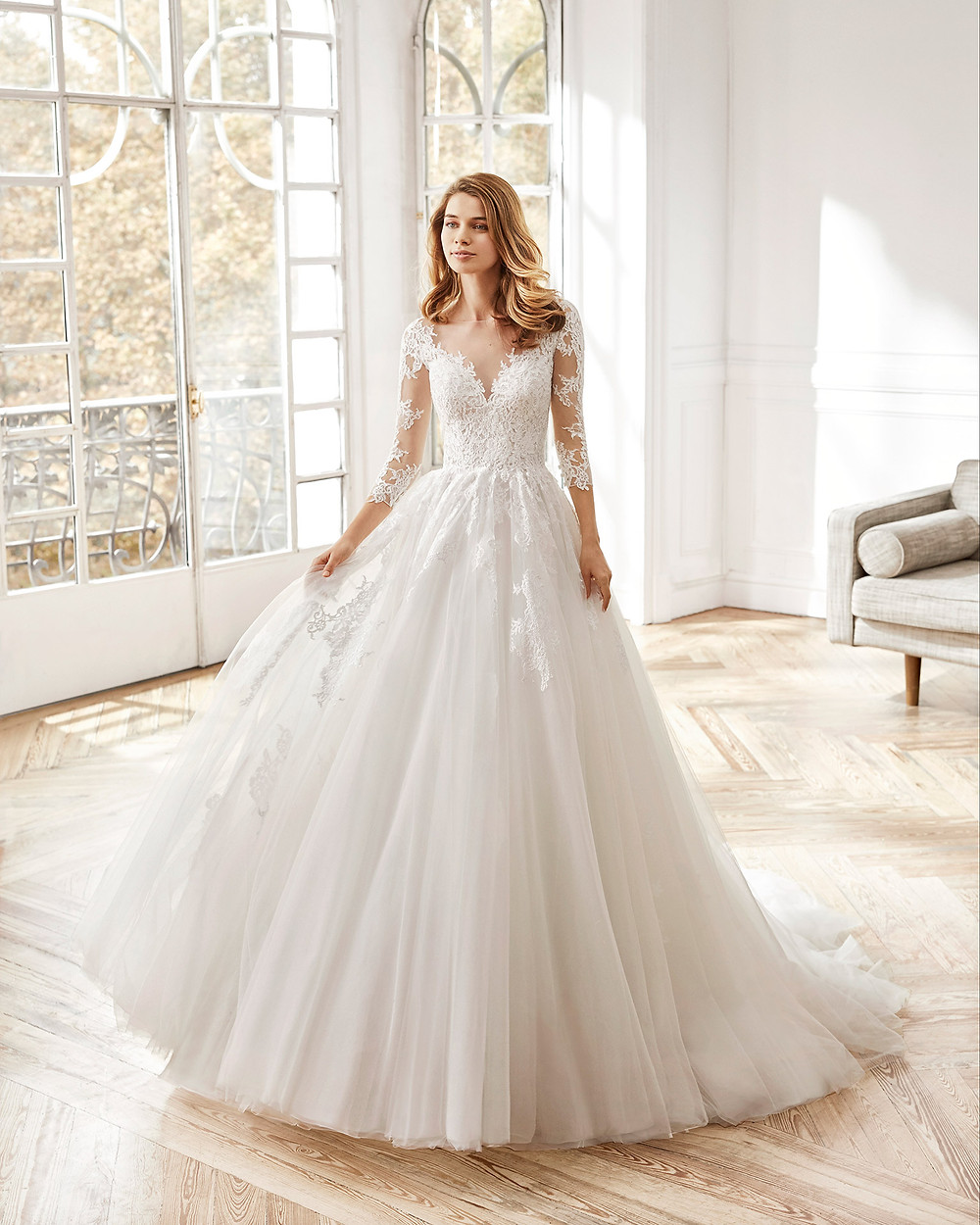 An Aire Barcelona 2020 lace and tulle princess ball gown wedding dress with long illusion sleeves and an illusion neckline