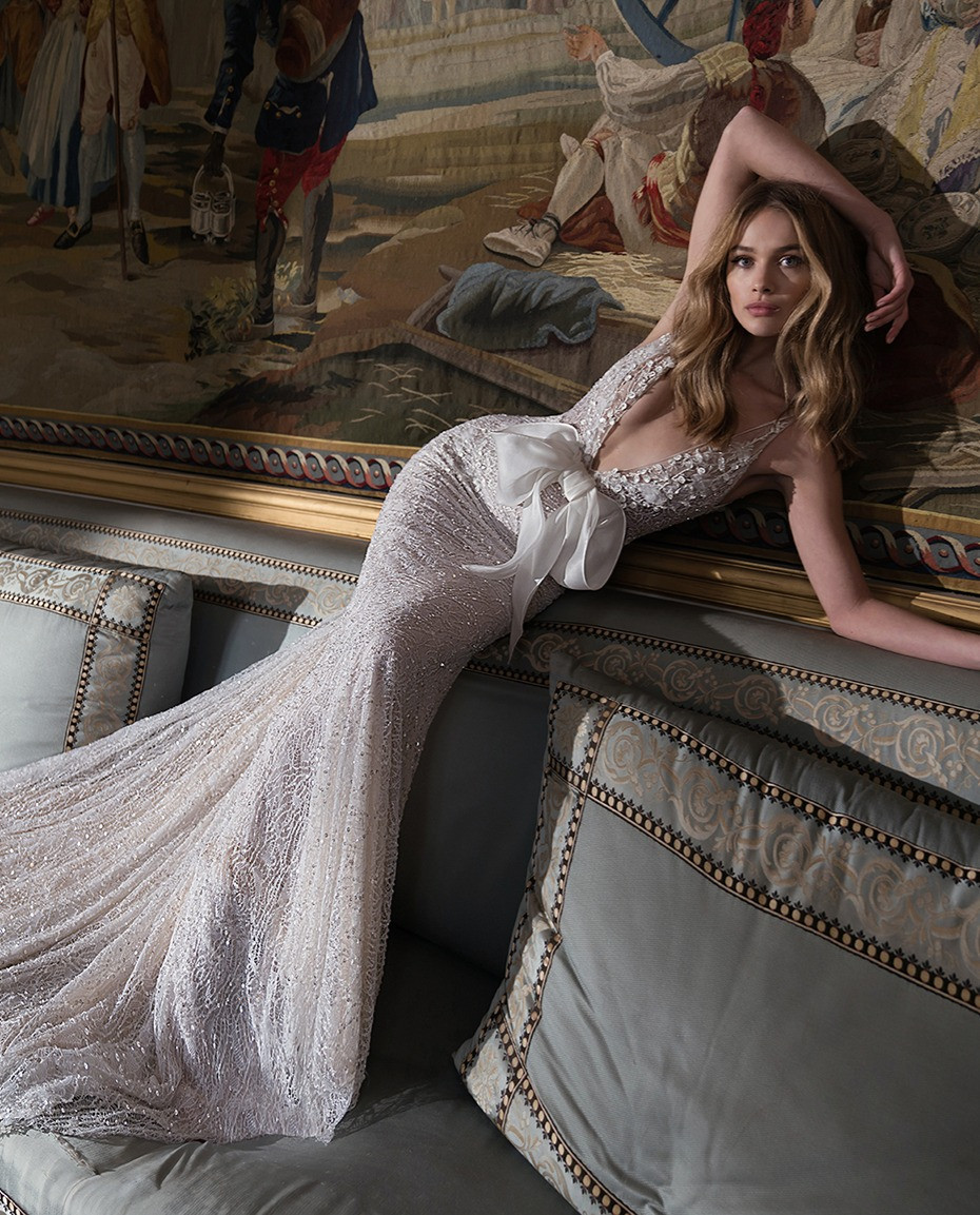 An Inbal Dror sparkly lace mermaid fit and flare wedding dress with a low v neckline and a bow