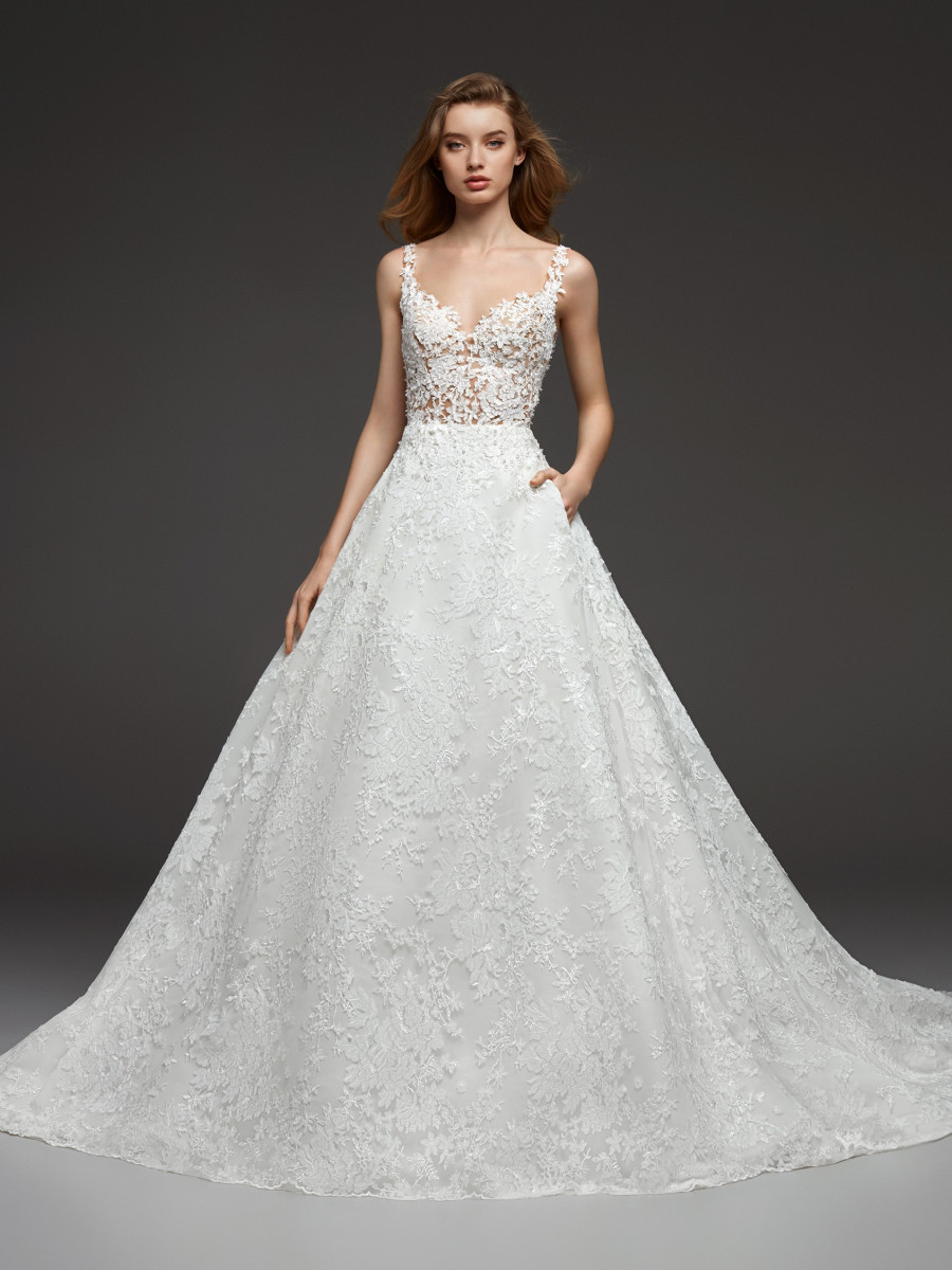 A Pronovias lace ball gown wedding dress with pockets and straps