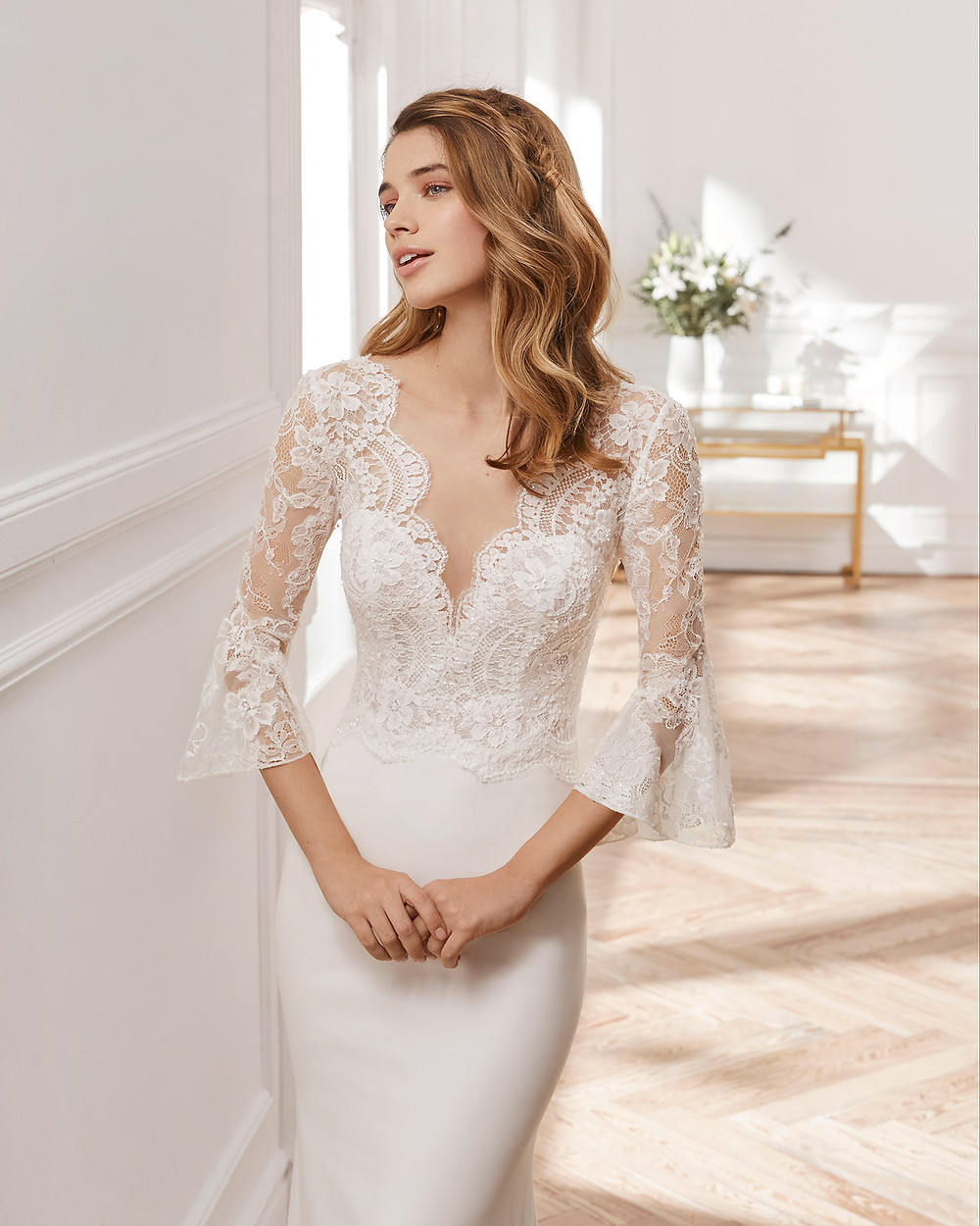 An Aire Barcelona 2020 lace and crepe mermaid fit and flare wedding dress with bell sleeves and a v neckline