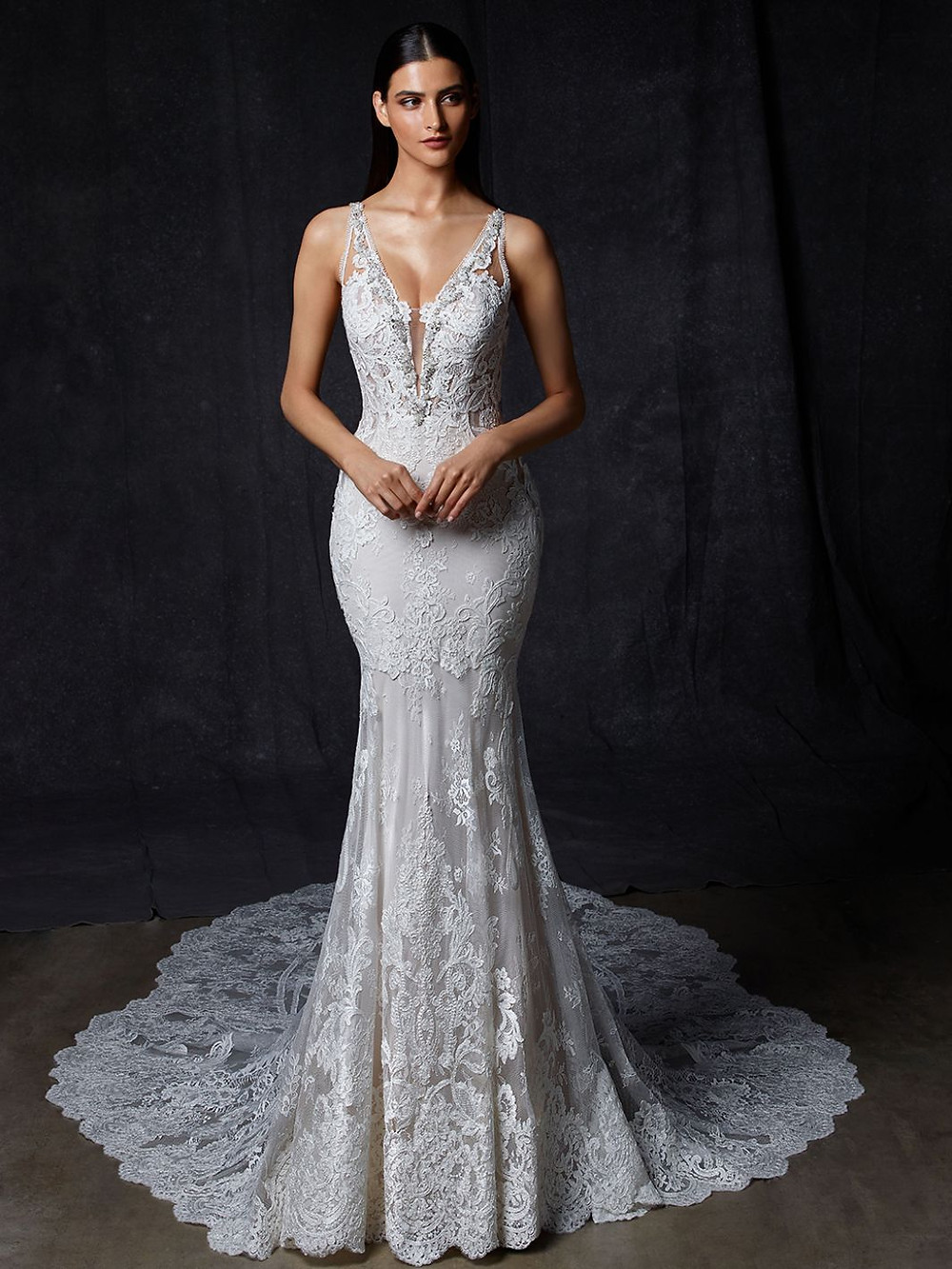 An Enzoani v neck, lace mermaid wedding dress with straps and a long train