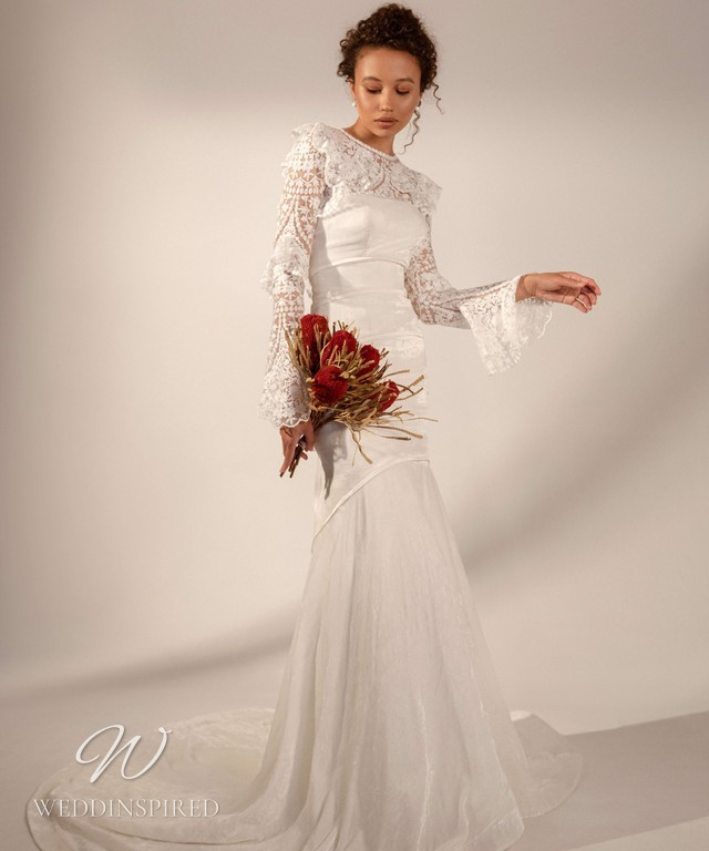 A Rara Avis 2021 modest lace and silk mermaid wedding dress with a high neck and long bell sleeves