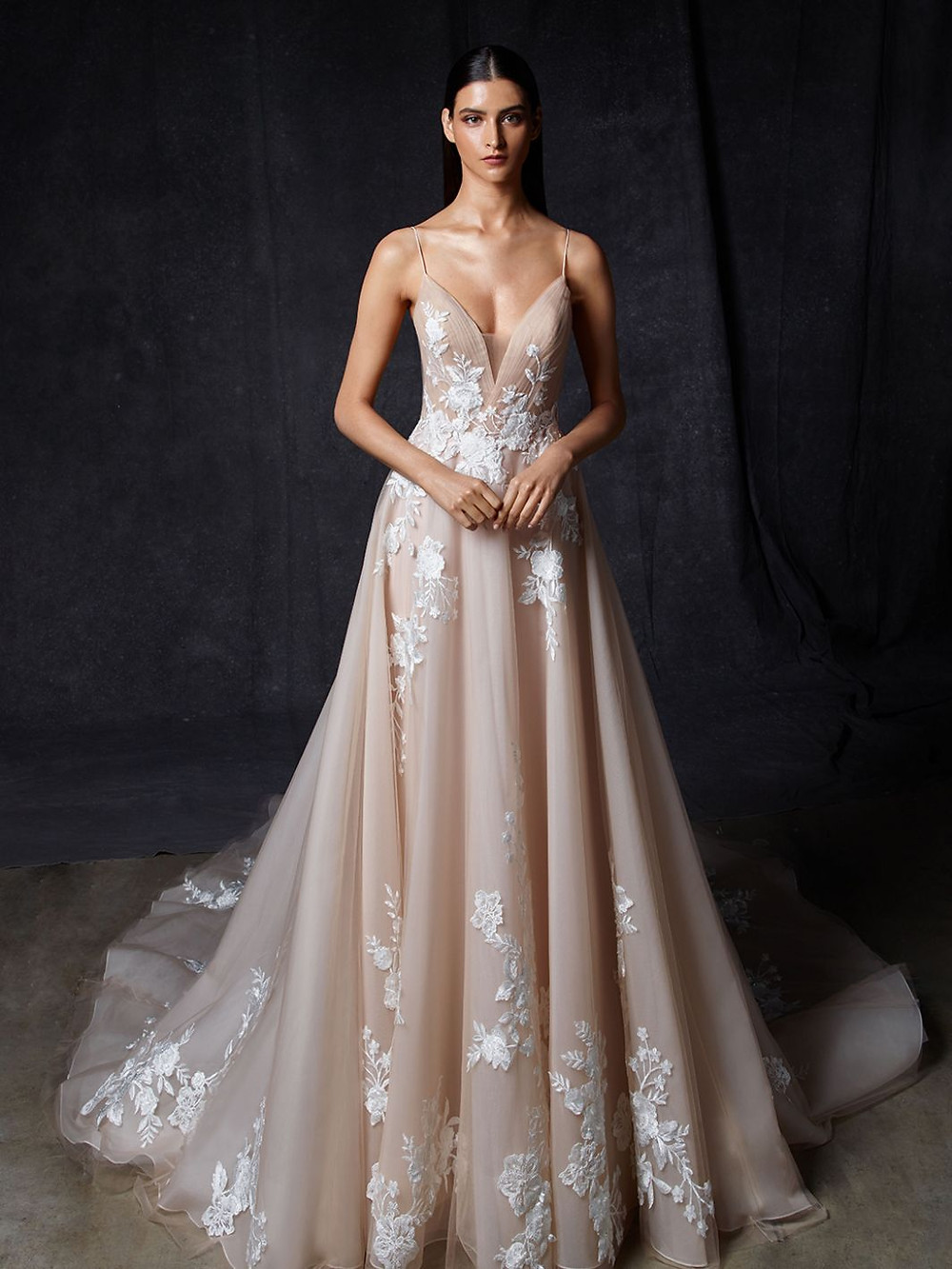 An Enzoani blush, tulle ball gown wedding dress with lace, thin straps and a long train