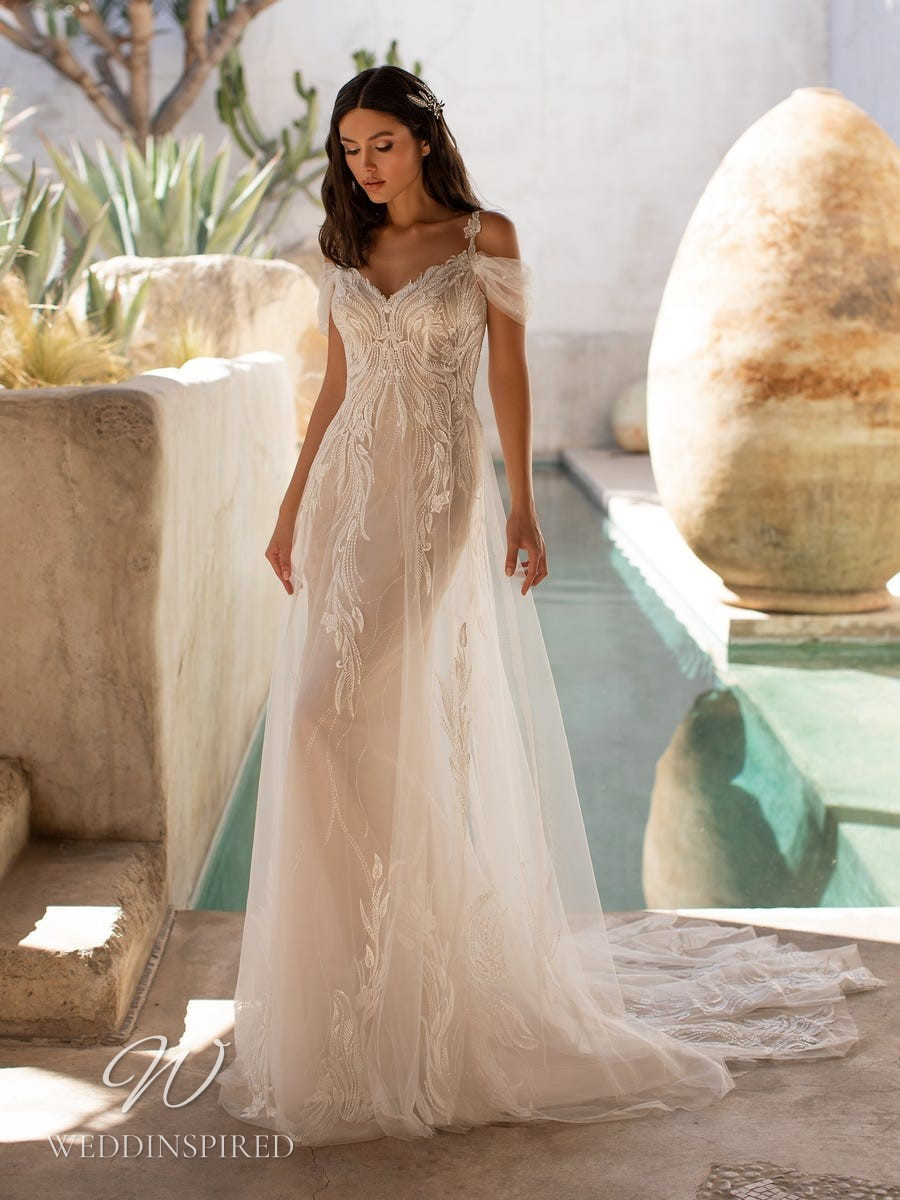 An Ashley Graham x Pronovias 2021 blush sparkly off the shoulder mermaid wedding dress