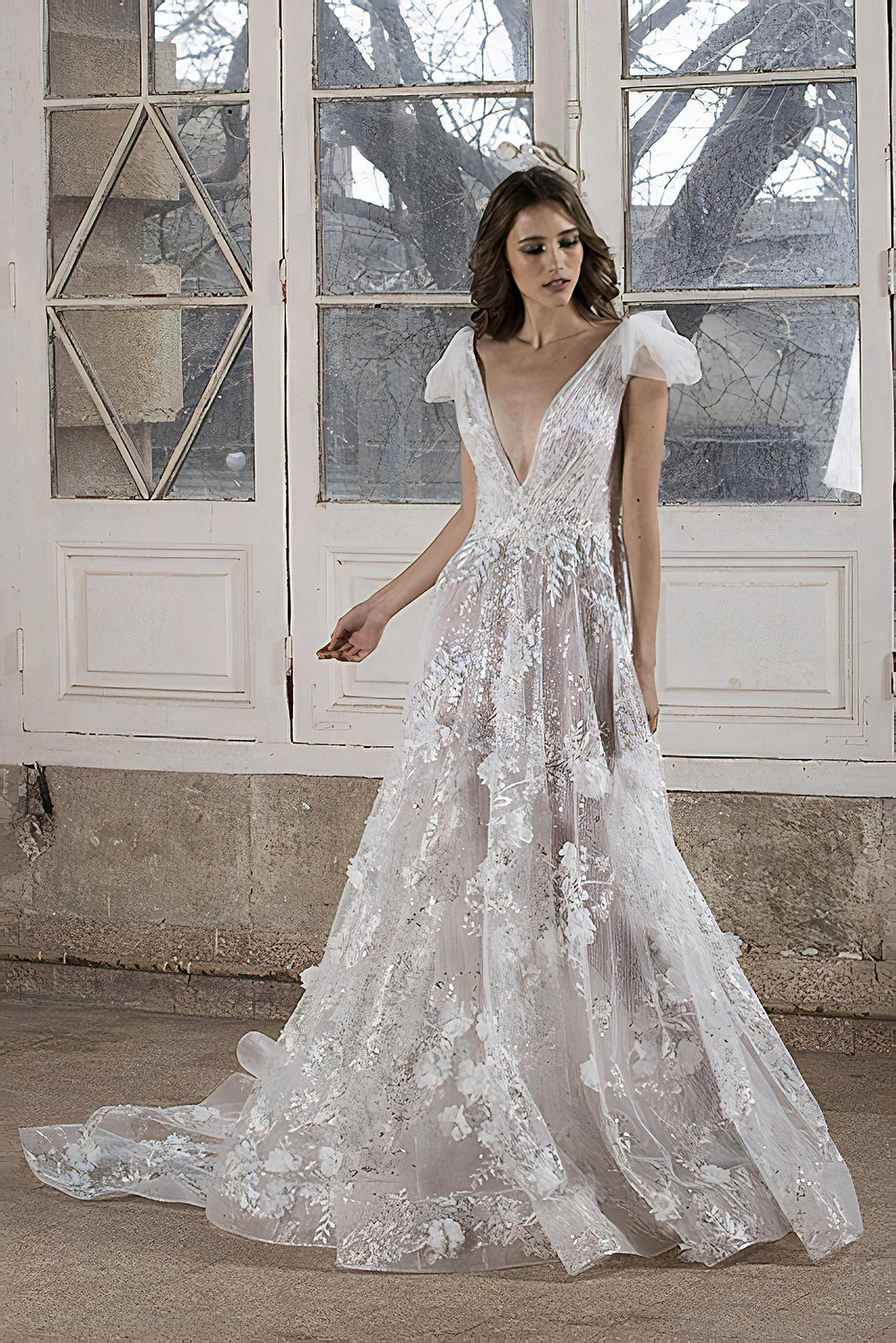 A deep-V wedding gown delicately enriched with silver embroidery and floral embellishments featuring tulle detailing on the shoulder